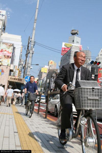 Vieux salaryman à vélo sous le soleil du Japon